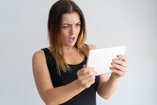 Besorgte frau, die tablettenschirm betrachtet