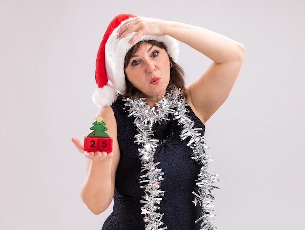 Besorgte frau mittleren alters mit weihnachtsmütze und lametta-girlande um den hals mit weihnachtsbaumspielzeug mit datum, das in die kamera schaut und die hand auf dem kopf isoliert auf weißem hintergrund mit kopienraum hält