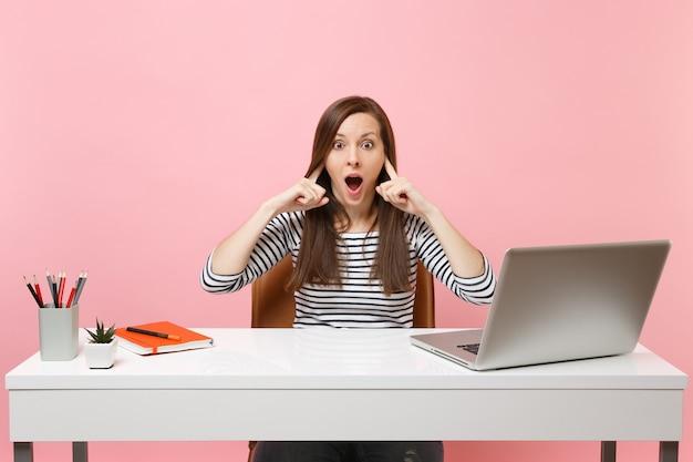 Besorgte frau möchte nicht zuhören, die ohren mit den fingern bedecken, sitzen und am weißen schreibtisch mit einem modernen pc-laptop arbeiten