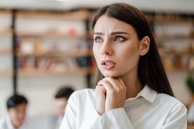 Besorgte geschäftsfrau im büro betroffen über unternehmenszukunft