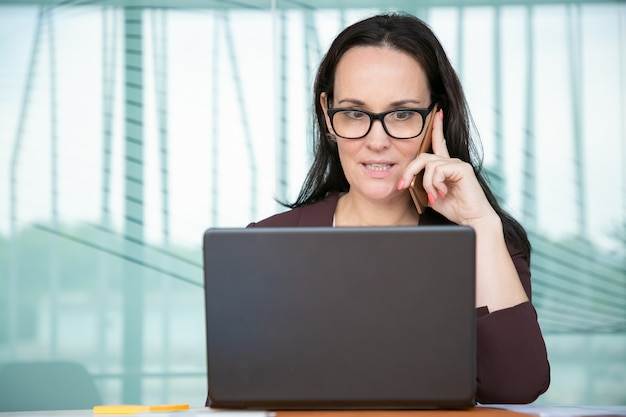 Besorgte geschäftsfrau in der brille, die auf handy spricht und große augen macht, am computer im büro arbeitet, laptop am tisch benutzt
