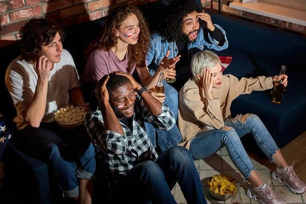 Besorgte jubelnde freunde oder basketballfans, die zu hause ein basketballspiel im fernsehen ansehen. freundschafts-, sport- und unterhaltungskonzept. junge leute sorgen sich um lieblingsmannschaft