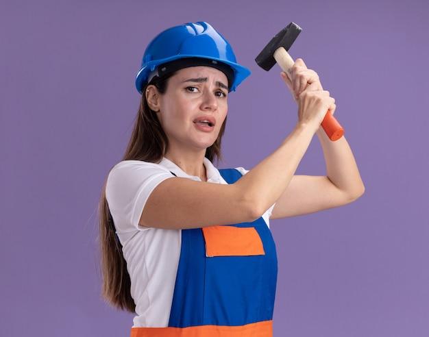 Besorgte junge baumeisterfrauen in uniform, die den hammer einzeln auf lila wand heben