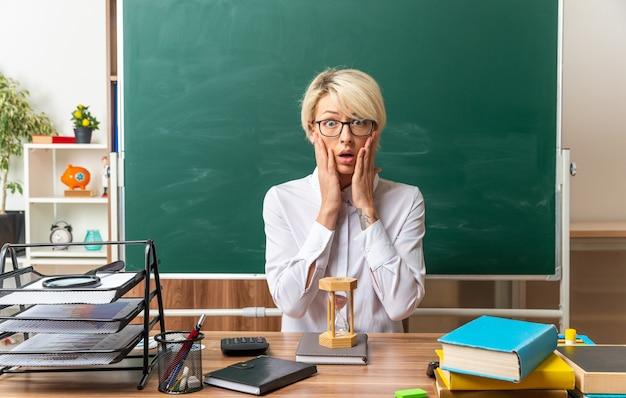 Besorgte junge blonde lehrerin mit brille sitzt am schreibtisch mit schulwerkzeugen im klassenzimmer und hält die hände auf dem gesicht