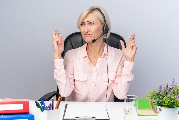 Besorgte junge callcenter-betreiberin mit headset am tisch sitzend mit bürowerkzeugen, die die finger kreuzen