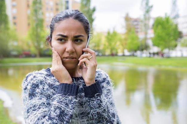 Besorgte junge frau, die auf smartphone im stadtpark spricht