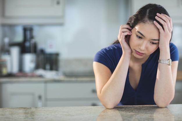 Besorgte junge frau, die in der küche sitzt