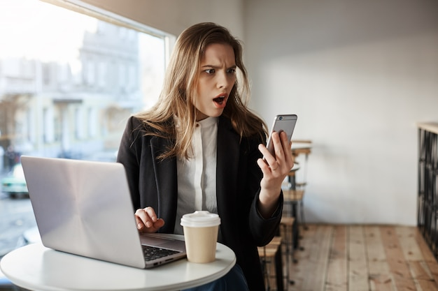 Besorgte junge geschäftsfrau im café, das das smartphone schaut