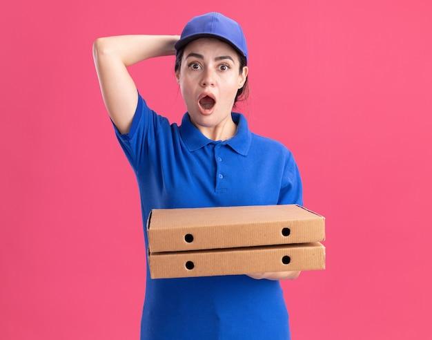 Besorgte junge lieferfrau in uniform und mütze, die pizzapakete hält, die hand hinter den kopf legt, isoliert auf rosa wand mit kopierraum