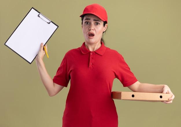 Besorgte junge lieferfrau in uniform und mütze mit pizzapaket, das klemmbrett mit bleistift in der hand zeigt