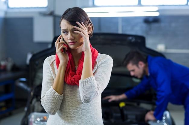 Besorgte kunden sprechen über handy während mechaniker auto im hintergrund der prüfung