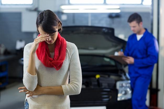 Besorgte kunden stehen, während mechaniker prüfung auto im hintergrund