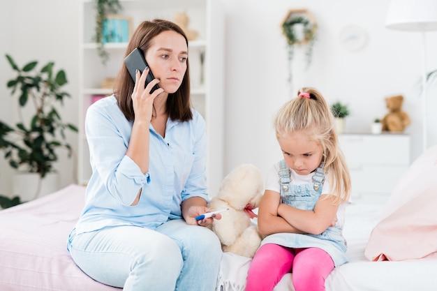 Besorgte mutter mit thermometer und smartphone ruft arzt nach hause, während sie neben ihrer kleinen kranken tochter sitzt
