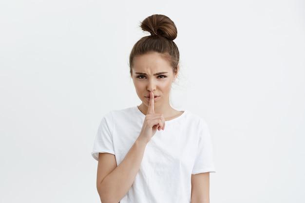 Besorgte niedliche europäische frau, die zeigefinger über lippen hält und bittet, ruhig zu bleiben, während sie die stirn runzelt