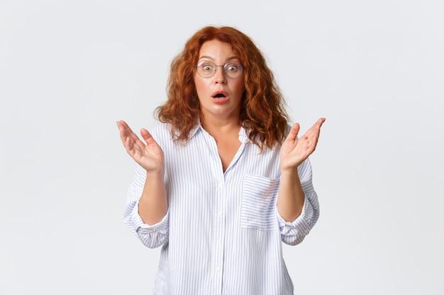 Besorgte und überfallene rothaarige frau in brille, frau mittleren alters reagiert auf schockierende nachrichten, hebt die hände und schnappt besorgt nach luft, ist alarmiert über die situation, weiße wand.