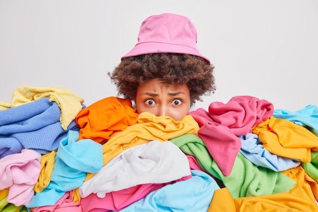 Besorgte verwirrte frau, die mit entfalteten, durcheinandergewirbelten kleidern vollgestopft ist, hebt den kopf aus einem haufen entfalteter bunter wäsche