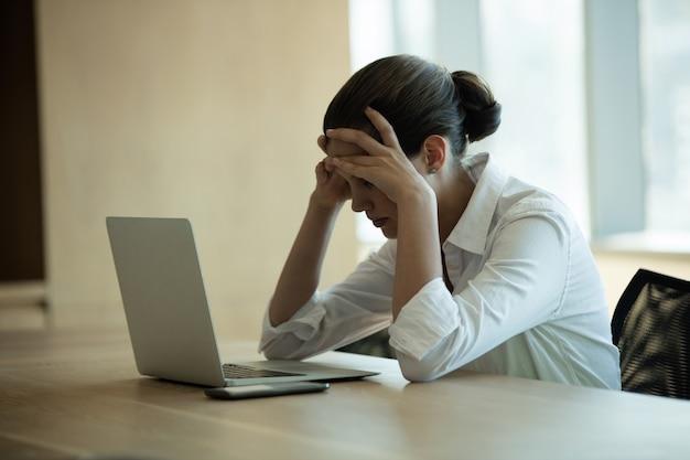 Besorgte weibliche geschäftsführerin mit laptop im konferenzraum