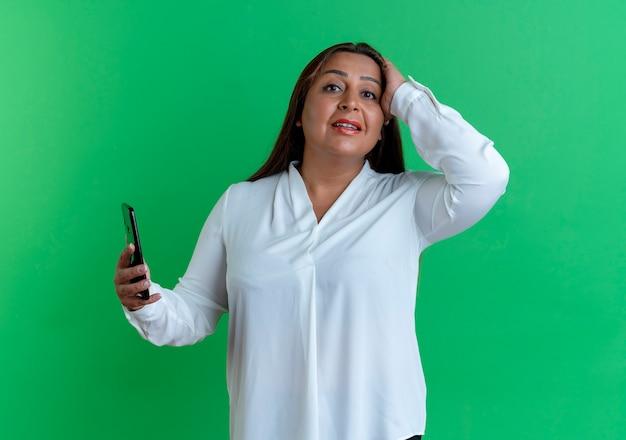 Besorgte zufällige kaukasische frau mittleren alters, die telefon hält und hand auf kopf legt