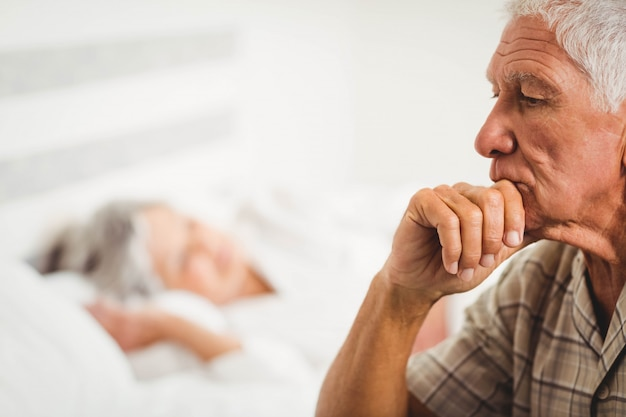 Besorgter älterer mann, der auf bett im schlafzimmer sitzt