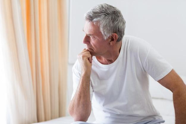 Besorgter älterer mann, der auf bett sitzt