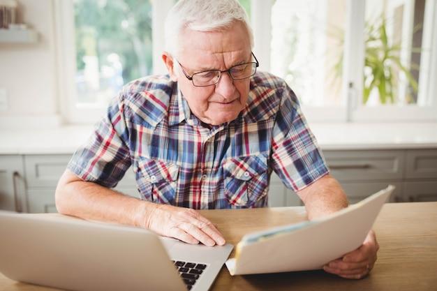 Besorgter älterer mann, der ein dokument bei der anwendung des laptops betrachtet