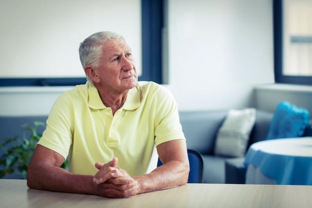 Besorgter älterer mann, der im wohnzimmer sitzt