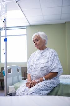 Besorgter älterer patient, der auf bett sitzt