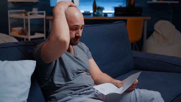 Besorgter ängstlicher junger mann, der eine schlechte nachricht im postbrief liest reading