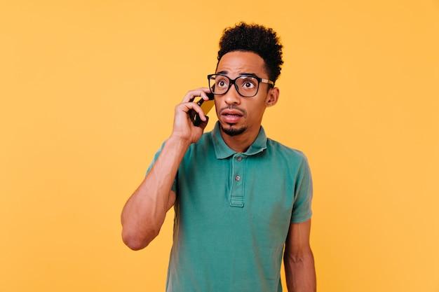 Besorgter afrikanischer kerl mit dem lockigen haar, das am telefon spricht. überraschtes schwarzes männliches modell, das mit offenem mund während des anrufs aufwirft.