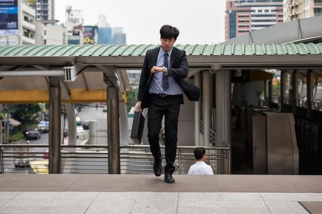 Besorgter asiatischer geschäftsmann laufen und betrachten uhr