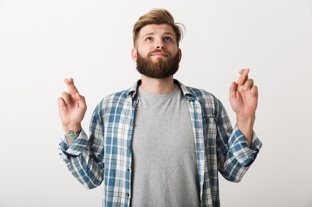 Besorgter bärtiger mann gekleidet im karierten hemd, das isoliert steht und daumen drückt für glück