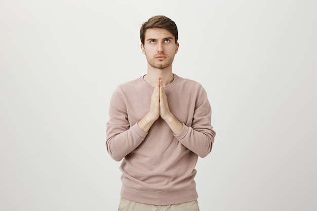 Besorgter, ernsthaft aussehender mann, der gott betet, hände flehend hält und aufschaut
