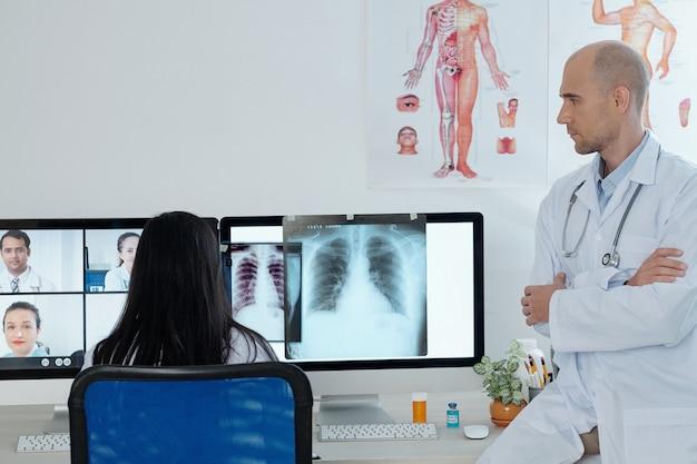 Besorgter ernsthafter arzt bespricht lungenröntgenaufnahme eines patienten mit vermutetem oder bestätigtem coronavirus