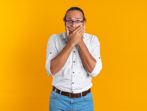 Besorgter erwachsener gutaussehender mann mit brille, der die kamera betrachtet, die den mund mit den händen bedeckt, die auf einer orangefarbenen wand mit kopienraum isoliert sind