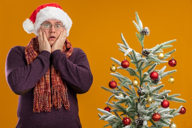 Besorgter erwachsener mann mit brille und weihnachtsmütze mit schal um den hals, der in der nähe des dekorierten weihnachtsbaums steht und die hände auf dem gesicht isoliert auf oranger wand hält