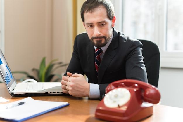 Besorgter geschäftsmann, der auf einen telefonanruf wartet