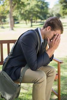 Besorgter geschäftsmann, der auf parkbank sitzt