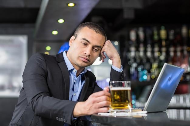Besorgter geschäftsmann, der ein bier trinkt