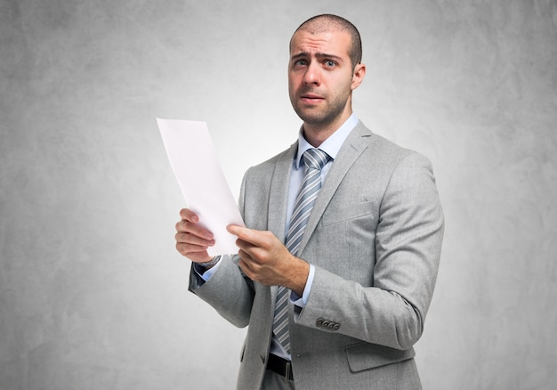 Besorgter geschäftsmann, der ein dokument anhält