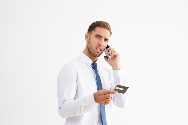 Besorgter geschäftsmann, der kreditkarte und die unterhaltung hält
