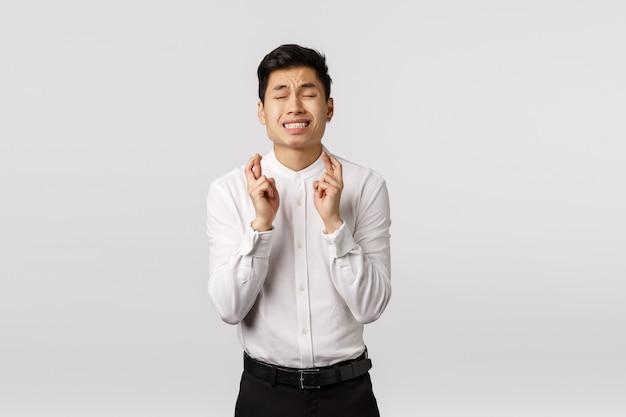 Besorgter, hoffnungsvoller und alarmierter junger asiatischer mann, der gott betet und um gnade oder wunsch bittet, gehen in erfüllung, nahe augen kreuzen finger viel glück, traumrelish etwas, unterzeichnen große sache