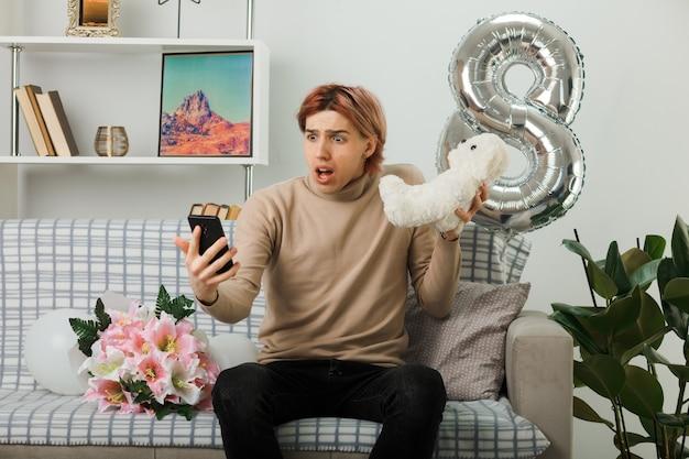 Besorgter hübscher kerl am glücklichen frauentag, der teddybären hält, der auf das telefon in seiner hand schaut, das auf sofa im wohnzimmer sitzt