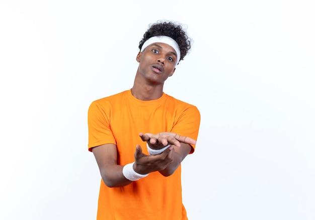 Besorgter junger afroamerikanischer sportlicher mann, der stirnband und armband mit ausgestreckten händen trägt