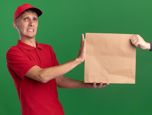 Besorgter junger blonder lieferjunge gibt jemandem papierpaket