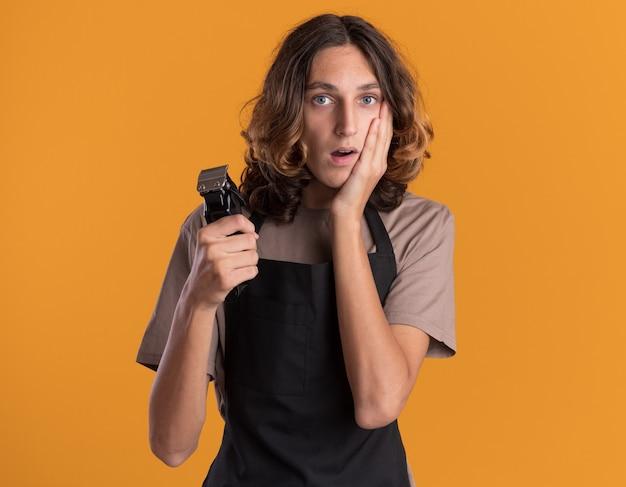 Besorgter junger gutaussehender friseur in uniform, der haarschneidemaschinen hält und die hand auf dem gesicht hält