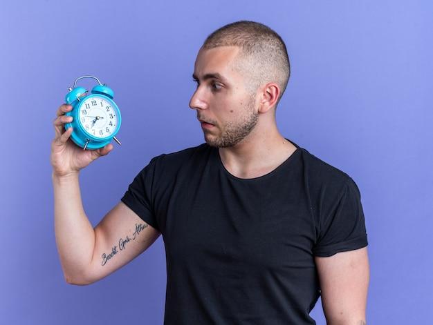 Besorgter junger gutaussehender kerl mit schwarzem t-shirt, der den wecker auf blauem hintergrund hält und anschaut