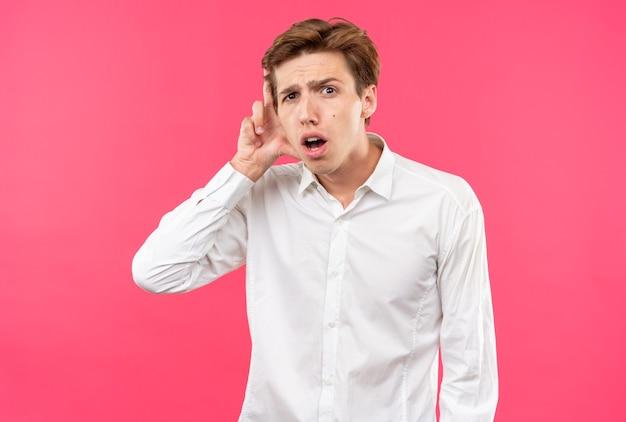Besorgter junger gutaussehender kerl mit weißem hemd, der hand aufs ohr legt