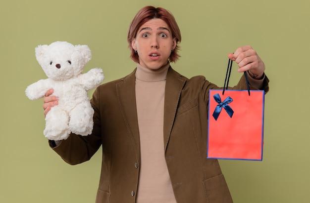 Besorgter junger gutaussehender mann mit weißem teddybär und geschenktüte