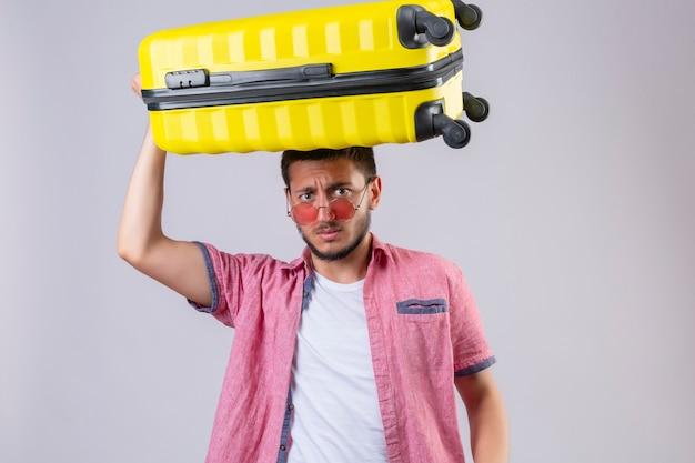 Besorgter junger hübscher reisender kerl, der sonnenbrille trägt, die mit koffer auf seinem kopf steht und kamera mit angstausdruck über weißem hintergrund betrachtet