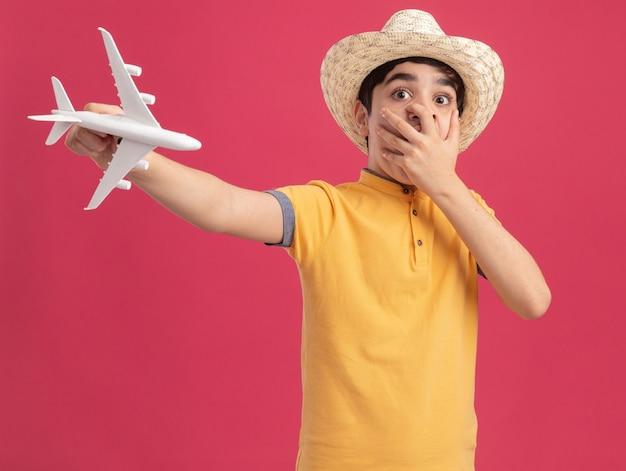 Besorgter junger kaukasischer junge mit strandhut, der das modellflugzeug ausstreckt und geradeausschaut und die hand auf den mund hält